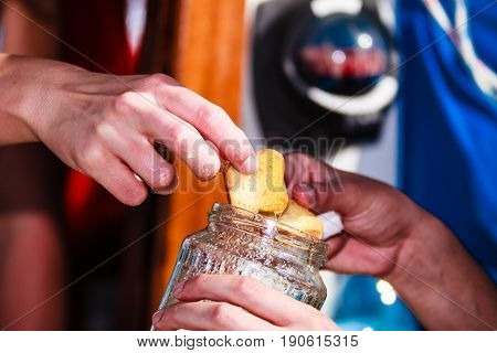 Man picking rusk biscuit from glass jar. Eating food during traveling concept.
