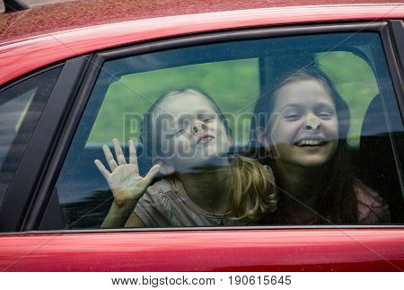 children making funny faces sitting at the car