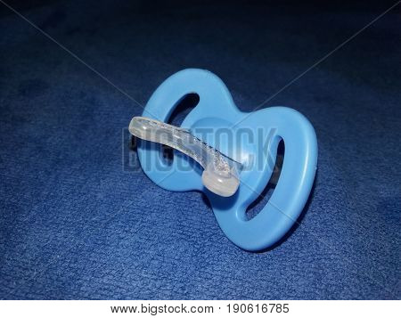 blue teething toy for two months old baby on dar blue background