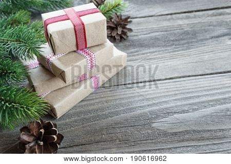 Christmas composition of pine cones spruce branches and stack of gift boxes tied with red ribbons on the background of old unpainted wooden boards; with copy-space