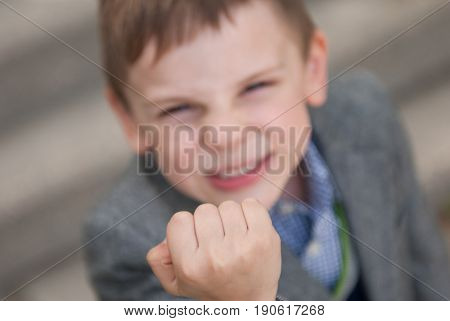 angry little boy with a grimace on his face threatens with his fist