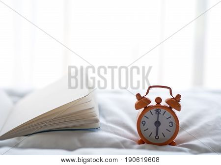 Alarm clock and book on bed in morning with sun light