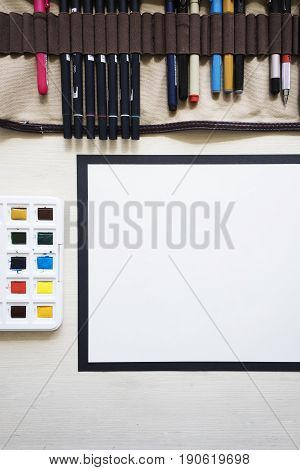 Top close up view on mock up of white blank paper on white wooden table background with markers in case dried yellow flowers brushes black scissors and watercolor palette. Vertical shot.
