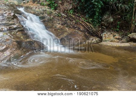 Huai Yang. Small waterfall with water motion in deep rain forest.