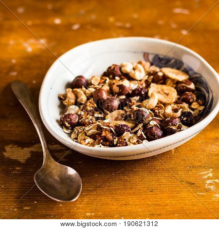 Organic granola or muesli with oat flakes, dried fruits and nuts in a bowl for breakfast on a wooden table, selective focus