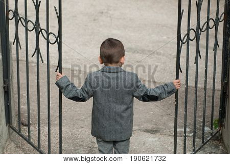 Little boy opening old wrought-iron black gate