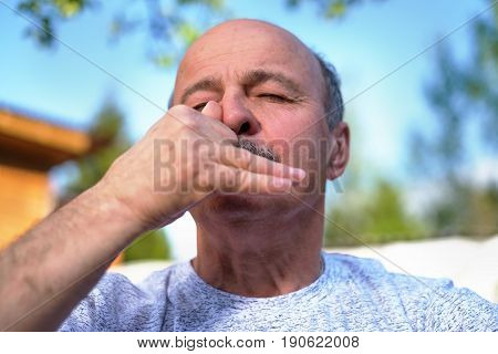 Handsome mature man with mustache breathing yoga pranayama on summer sunny day outside.