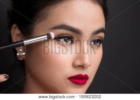 Close Up Of Hand Of Asian Woman Applying Eyeshadow On Female Eyelid.