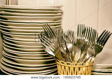 A stack of washed dishes and forks in the kitchen.