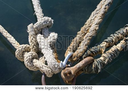 Rusted mooring ring with naval ropes on the pier