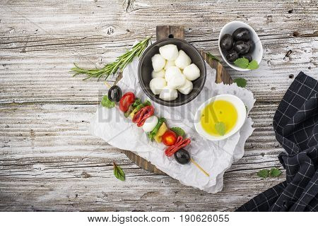 Healthy snack: mouth-watering kebabs on a picnic with tomatoes, mozzarella, salami, black olives, Basil, tortellini pasta on a cutting Board on wooden background with olive oil and herbs. From the top view. The concept of seasonal light supply.