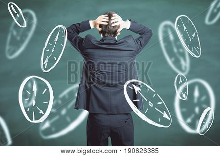 Back view of stressed young businessman on chalkboard background with drawn clocks. Deadline concept