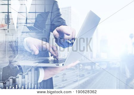 Side view of businessmen using laptop on abstract city background. Meeting concept. Double exposure