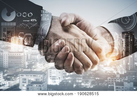 Close up of handshake on city background with forex chart. Deal concept. Double exposure