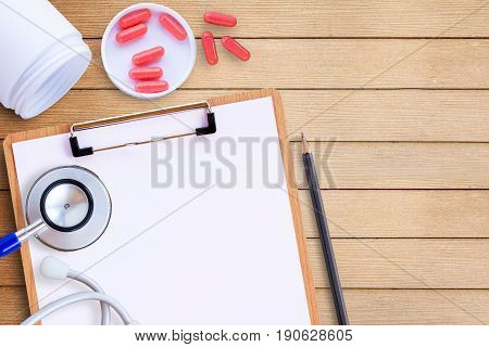 Medical equipment with pills on wooden doctor desk background horizontal medical concept. top view with copy space for any design health concept