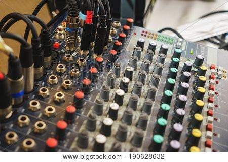 Special musical equipment for concerts, organization of events. Sound equipment on site with connected audio cables. Mixer console for the sound engineer, entertainment activities and performances of the musical group.