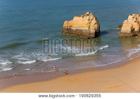PRAIA DA ROCHA, PORTUGAL - APRIL 23, 2017: People at the beach of Praia da Rocha in Portimao. This beach is a part of tourist region of Algarve.