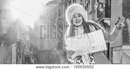 Woman In Venice, Italy In Winter Holding Map And Pointing