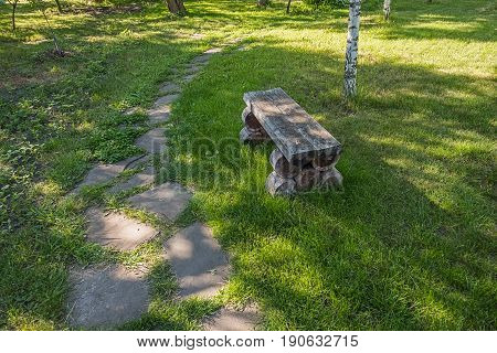 Old handmade wooden bench standing on lawn near white birch in the park or garden close to the right turn of sandstone footpath.