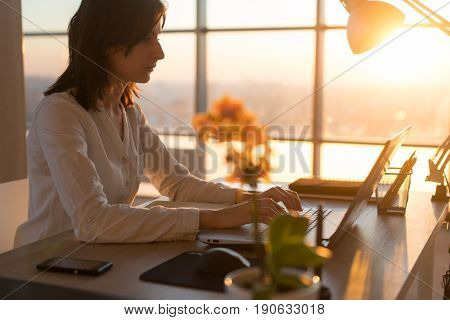 Concentrated female employee typing at workplace using computer. Side view portrait of a copywriter working on pc home
