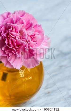 Pink artificial flower in brown round bottle on marble floor.