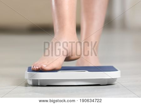 Woman standing on scales on wooden floor. Concept of weight loss