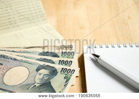 Bank passbook with japanese yen and book with pen on wood table background