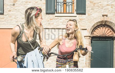 Happy female friends couple having fun riding bicycle in city old town - Friendship concept with young girlfriend on funny attitude biking together in summer spring time - Bright afternoon tone filter
