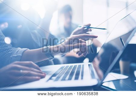 Business meeting concept.Closeup view of coworkers team working with mobile computer at modern office.Analyze business plans, using laptop.Blurred background.Horizontal.Cropped