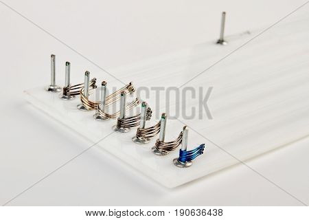 Row of fishing hooks on board. Different hooks for fisherman. Angling equipment.