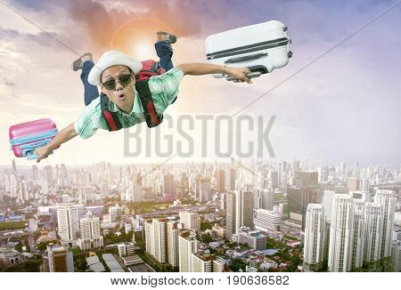 happiness face of asian traveling man flying with two luggage bag floating mid air over town skyscraper