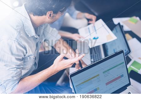 Closeup view of Group of young coworkers working together in modern office studio.Businessman talking with partners about new startup project.Horizontal, blurred background