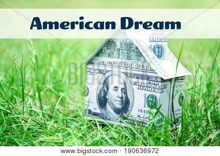 Text AMERICAN DREAM and money house on green grass, closeup