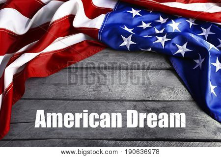 Text AMERICAN DREAM and USA flag on wooden background