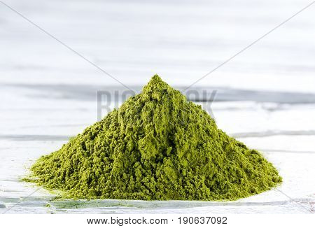 Heap of green matcha tea powder on white weathered wooden background