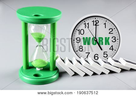 Clock with hourglass and dominoes on gray background. Concept of work time