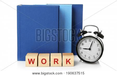 Wooden cubes with word WORK, alarm clock and books on white background. Business concept