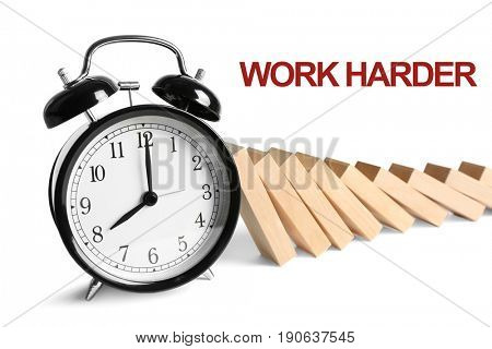 Alarm clock with falling dominoes and text WORK HARDER on white background. Business concept