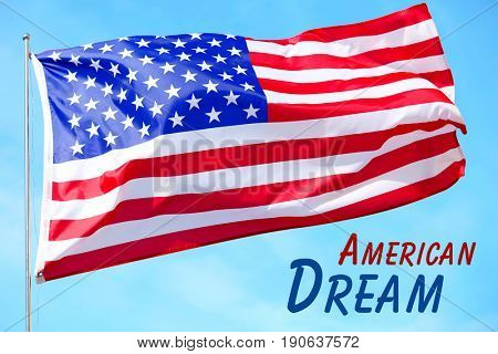 Text AMERICAN DREAM and waving USA flag on sky background