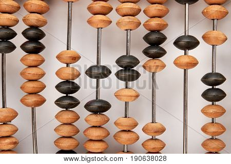 Close up wooden abacus, white background. Accountancy and business expenses.