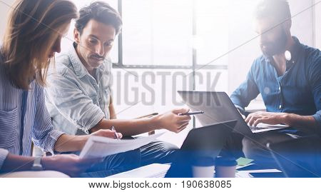 Group of three young coworkers working together at modern coworking studio.Woman pointing hand on paper document and talking with man about new startup project.Horizontal, blurred background