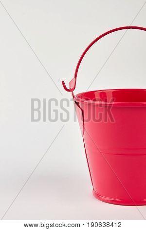 Cropped image of red bucket. Aluminium garden bucket on white background.