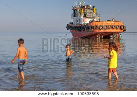Bandar Abbas Hormozgan Province Iran - 16 april 2017: Three children of about 7 years old playing in the water against a tugboat aground.