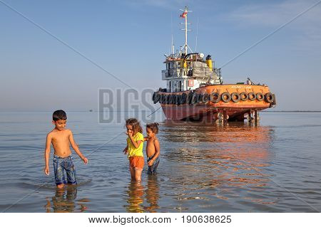Bandar Abbas Hormozgan Province Iran - 16 april 2017: One boy is about 7 years old and two little girls play in the shallow waters of the Persian Gulf not far from ran aground industrial boat.