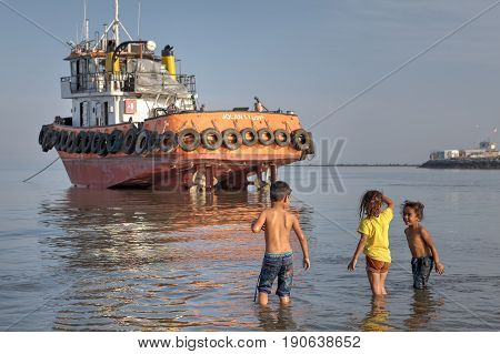 Bandar Abbas Hormozgan Province Iran - 16 april 2017: Iranian children play in the shallows near the boat which ran aground.