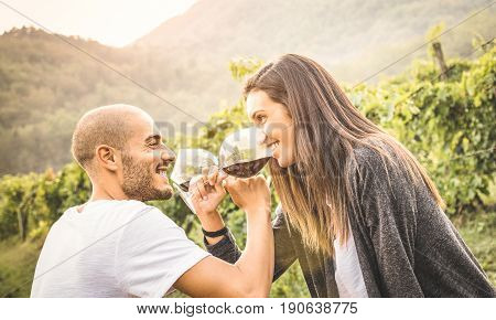 Happy young couple of lover drinking red wine at vineyard farmhouse - Handsome man looking at beautiful woman eyes - Alternative relationship concept with boyfriend and girlfriend having fun together