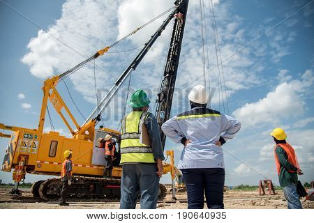 Engineer and foreman looking at heavy machine Assembly concrete pile driving truck for working against building construction crane
