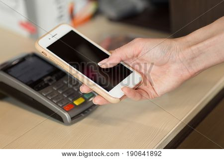 Close-up Of Woman Making Payment Through Nfc In Cafeteria