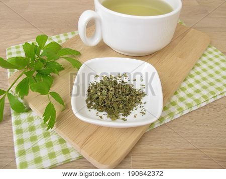 Cup of herbal tea with lovage and lovage leaves