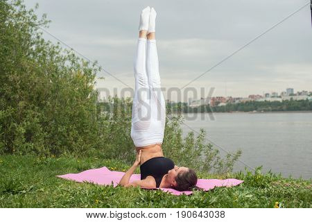Fit woman making yoga in shoulderstand pose exercising in nature.